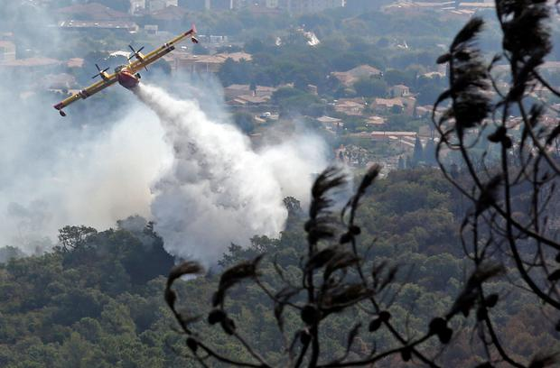 A Canadair firefighting plane releases water to extinguish a wildfire in Bormes-les-Mimosas, in the Var department, France, July 27, 2017. REUTERS/Jean-Paul Pelissier
