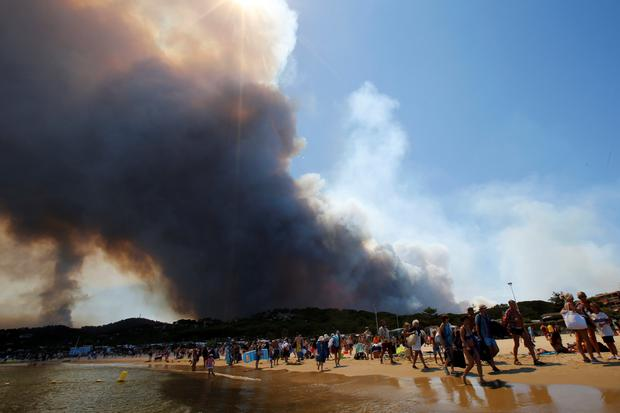 Tourists evacuate the beach as smoke fills the sky above a burning hillside in Bormes-les-Mimosas, in the Var department, France, July 26, 2017. REUTERS/Jean-Paul Pelissier