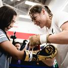 Photo of Katie Taylor with a young fans at #BronerGarcia workouts at Modell's Sporting Goods. Photo by Amanda Westcott.
