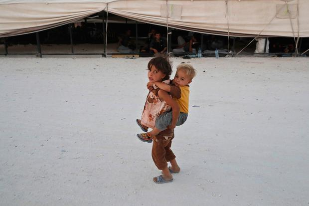A displaced child who fled fighting in Raqqa, carries a boy on her back in a refugee camp, in Ain Issa, northeast Syria. (AP Photo/Hussein Malla)