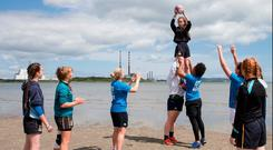 Sophie Spence, Niamh Briggs and Nora Stapleton help fitness instructor Pat Divilly put a group of enthusiastic young rugby players through their paces on Sandymount Strand. Photo: David Conachy