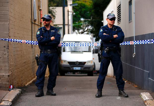 Police officers block a small alley where police vans are parked at a home being searched after Australian counter-terrorism police arrested four people in raids late on Saturday across several Sydney suburbs in Australia, July 30, 2017. REUTERS/David Gray