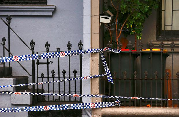 Police tape can be seen attached to the front fence of a home being searched after Australian counter-terrorism police arrested four people in raids late on Saturday across several Sydney suburbs in Australia, July 30, 2017. REUTERS/David Gray