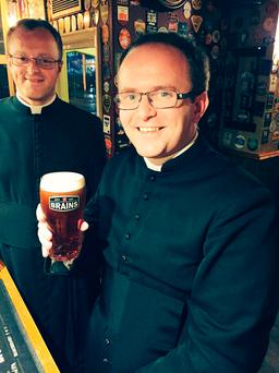 Undated handout photo of Reverend Rob James with a pint of Reverend James by Brain's. (PA)