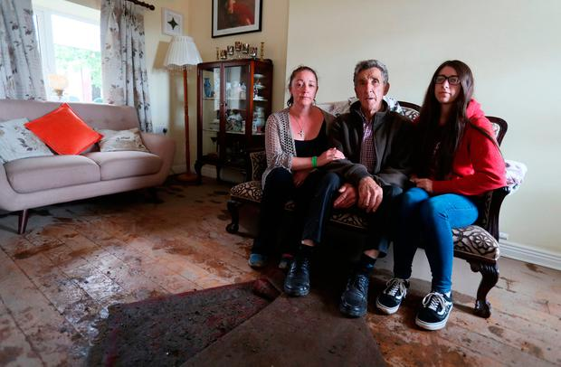 Jimmy Murtagh with daughter Sarah, left, and granddaughter Vicki at his flooded home. Photo: Brian Lawless/PA