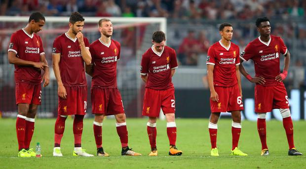 Liverpool players look dejected during the penalty shootout. REUTERS/Michael Dalder