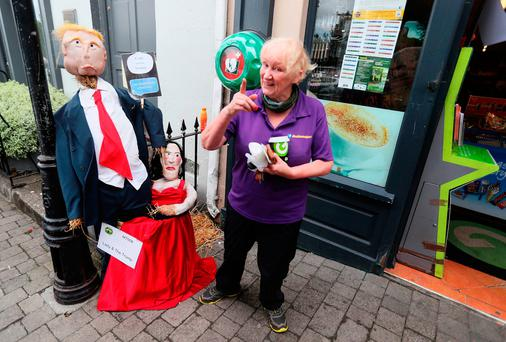 A woman passes a scarecrow entitled 'Lady and the Trump'. Photo: Brian Lawless