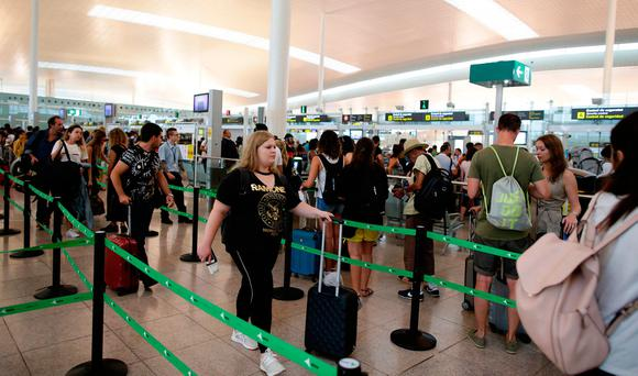 A long line of passengers waits to pass through security controls at Barcelona airport. Picture: PA