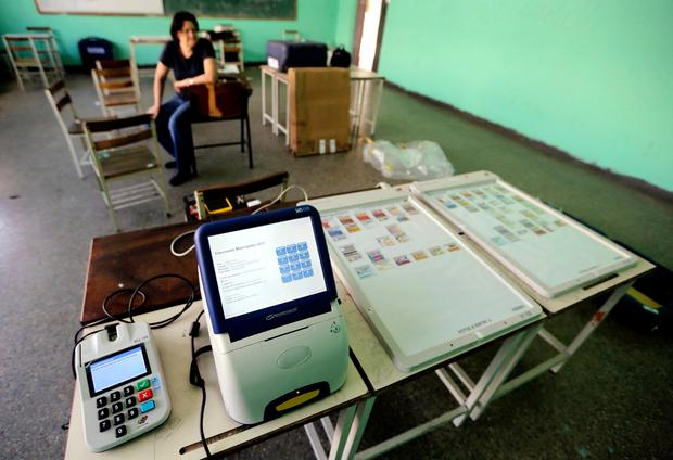A member of the Venezuelan National Electoral Council waits for a voting machine to charge during the preparation of a polling station in Caracas, Venezuela. Digital voting machines are in the spotlight in Venezuela, where a maker of election systems used in the country's tumultuous constituent-assembly election said Wednesday that the turnout figure had been