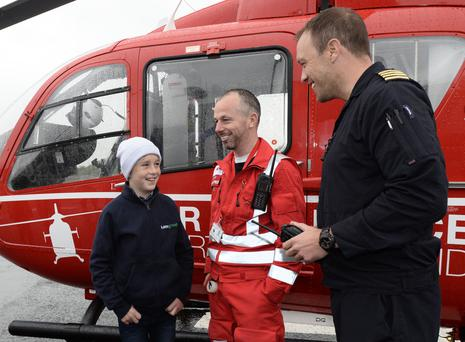 11-year-old Conor McMullan who was the first to be rescued by the new Air ambulance after a farming accident in Co Down with Paramedic Glenn O'roark and Pilot David O'Toole as the new Air Ambulance officially takes to the air at the old Maze prison Site in Lisburn.