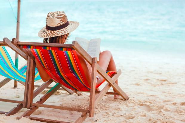 Young beautiful woman sitting on beach reading a book