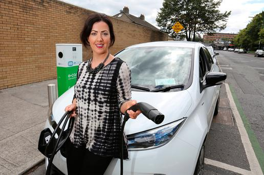Deirdre Reynolds with the Renault Zoe at the South Lotts Road EV charge point in Dublin. Photo: Frank McGrath
