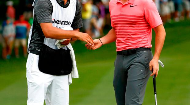 Rory McIlroy speaks to caddie Harry Diamond on the 18th green