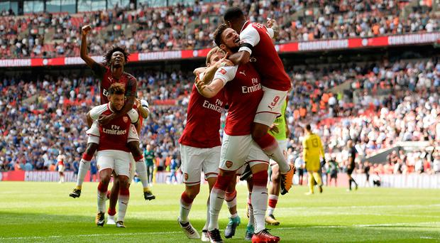 Arsenal's Olivier Giroud celebrates with teammates after scoring the winning penalty