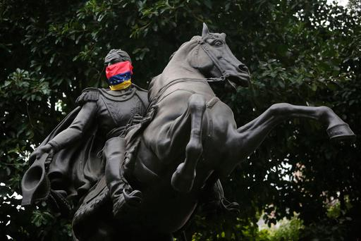 A statue of Venezuelan hero Simon Bolivar with a mask made with the Venezuelan flag is seen at Chacao square in Caracas, Venezuela (AP Photo/Wil Riera)