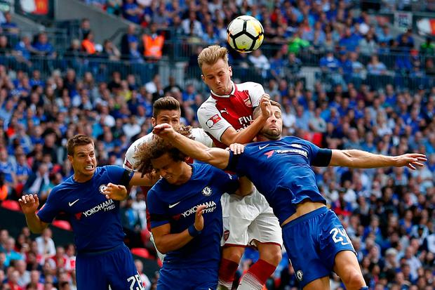 Arsenal's English defender Rob Holding (C) goes up for a header. Photo: Getty Images