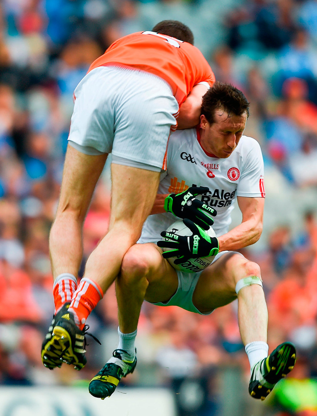 Tyrone's Colm Cavanagh protects the ball as he rides the collision with Armagh's Brendan Donaghy. Photo: Sportsfile