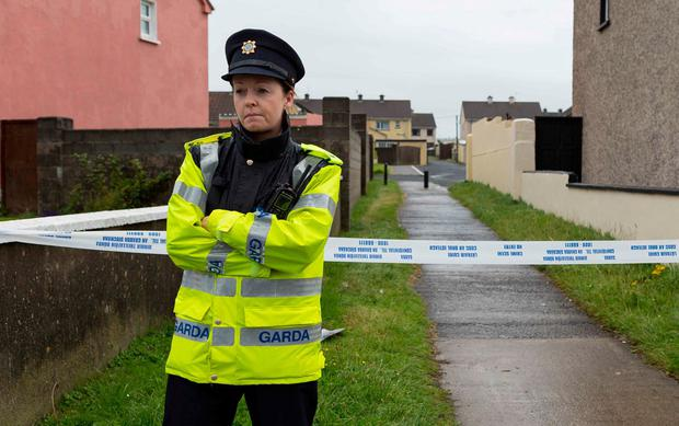A garda protects a laneway where Karl Haugh was stabbed. Photo: Eamon Ward