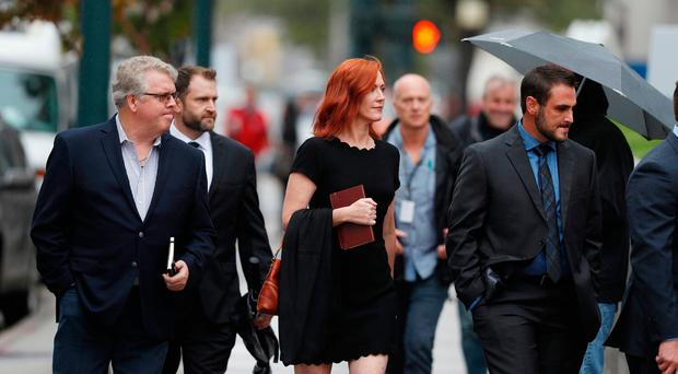 Surrounded by a phalanx of men, Tree Paine, center, publicist for Taylor Swift, walks in to attend the jury selection phase in a civil trial to determine whether a radio host groped the pop singer as the case opens. (AP Photo/David Zalubowski)