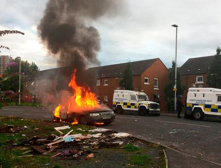 A parked car set alight by youths burns on Stewart Street in Belfast: David Young/PA Wire