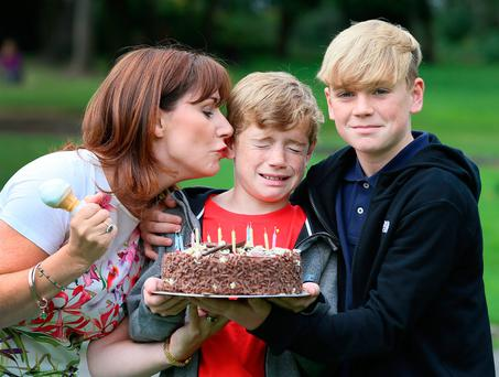 Josepha Madigan kisses her son Luke (12), who was celebrating his birthday with brother Daniel (13), at the Fine Gael picnic in Merrion Square to promote more affordable childcare. Photo: Frank McGrath