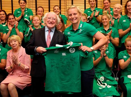 President Michael D Higgins is presented a signed Ireland jersey by captain Claire Molloy. Photo: Dan Sheridan/Inpho
