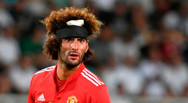 Manchester United's Belgian midfielder Marouane Fellaini already created some interesting images with a head band on his distinctive hair during Tuesday night's Super Cup clash with Real Madrid. / AFP PHOTO / Nikolay DOYCHINOVNIKOLAY DOYCHINOV/AFP/Getty Images
