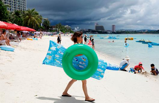 Tourists enjoying themselves along the Tumon beach on the island of Guam in the Pacific. Photo: Reuters