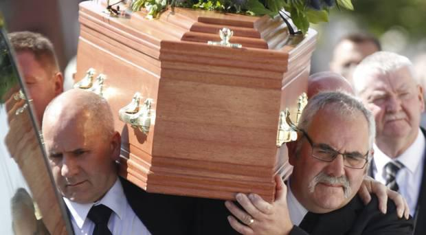Friends and family carry the coffin of James Moore following his funeral service. Image: Belfast Telegraph.