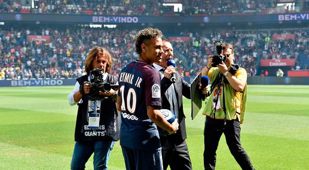 Paris Saint-Germain's Brazilian forward Neymar poses with a ball during his presentation to the fans at the Parc des Princes stadium in Paris on August 5, 2017. Photo - ALAIN JOCARD/AFP/Getty Images.