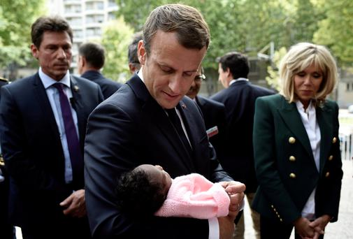 French President Emmanuel Macron, flanked by his wife Brigitte, holds a baby as he visits the Robert-Debré paediatric hospital in Paris this week. Photo: Reuters
