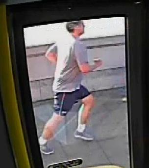 A CCTV image of the jogger sought by police over an incident in which a woman pedestrian was pushed into the path of a bus.