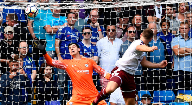 Burnley's Sam Vokes heads their third goal past Chelsea goalkeeper Thibaut Courtois at Stamford Bridge yesterday. Photo: Dylan Martinez/Reuters