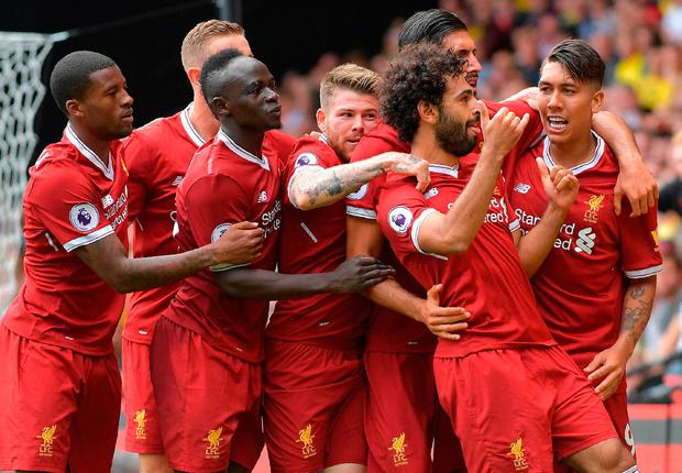 Liverpool's Egyptian midfielder Mohamed Salah (2R) is mobbed by teammates as he celebrates scoring his team's third goal Photo: Getty
