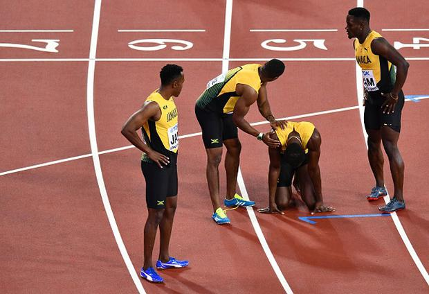Jamaica's Usain Bolt (2R) reacts after injuring himself as team-mates try to help him during the final of the men's 4x100m relay athletics event at the 2017 IAAF World Championships at the London Stadium in London on August 12, 2017. / AFP PHOTO / Antonin THUILLIER (Photo credit should read ANTONIN THUILLIER/AFP/Getty Images)