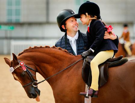 Saoirse O'Neill (7) is congratulated by her dad Michael after she competed at the RDS yesterday. Photo: Gerry Mooney