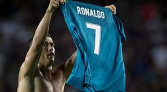 Real Madrid's Portuguese forward Cristiano Ronaldo shows his jersey to celebrate his goal during the first leg of the Spanish Supercup football match between FC Barcelona and Real Madrid CF at the Camp Nou stadium in Barcelona on August 13, 2017. / AFP PHOTO / STRINGER (Photo credit should read STRINGER/AFP/Getty Images)