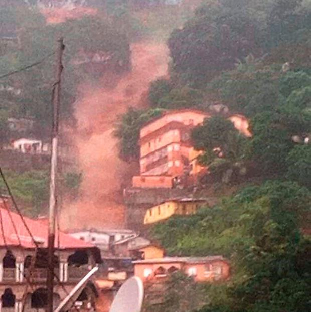In this image made available by Society 4 Climate Change Communication, Sierra Leone, mud and water cascades down the side on a hill in Freetown, Sierra Leone (Society 4 Climate Change Communication via AP)