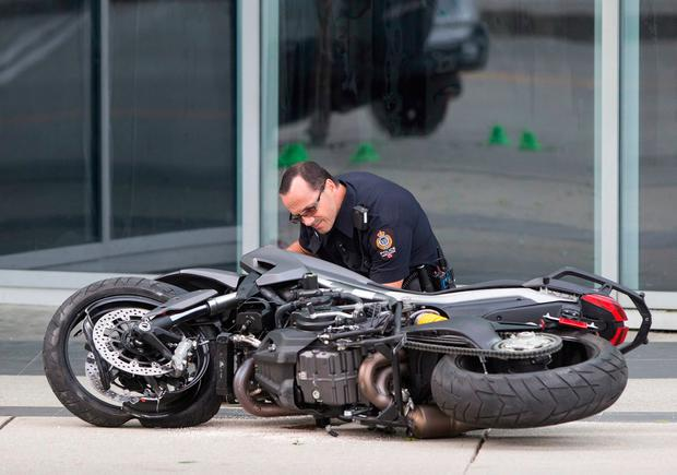 A police officer examines a motorcycle after a female stunt driver working on the movie