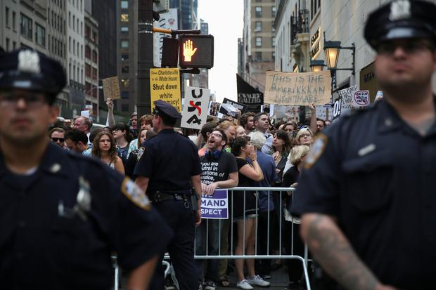 New York Police Department (NYPD) officers cordon off some thousands of anti-Trump activists who were staging a demonstration outside Trump Tower ahead of the arrival of U.S. President Donald Trump in Manhattan, New York, U.S., August 14, 2017. REUTERS/Amr Alfiky