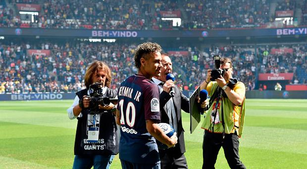Paris Saint-Germain's Brazilian forward Neymar poses with a ball during his presentation to the fans at the Parc des Princes stadium in Paris on August 5, 2017. Brazil superstar Neymar will watch from the stands as Paris Saint-Germain open their season on August 5, 2017, but the French club have already clawed back around a million euros on their world record investment. Neymar, who signed from Barcelona for a mind-boggling 222 million euros ($264 million), is presented to the PSG support prior to his new team's first game of the Ligue 1 campaign against promoted Amiens. / AFP PHOTO / ALAIN JOCARD (Photo credit should read ALAIN JOCARD/AFP/Getty Images)