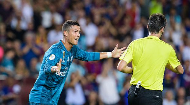 Cristiano Ronaldo of Real Madrid (L) gestures after gets a red card from Fifa Referee Ricardo de Burgos Bergoetxea (R) during the Supercopa de Espana Final 1st Leg match between FC Barcelona and Real Madrid at Camp Nou on August 13, 2017 in Barcelona, Spain. (Photo by Marcio Rodrigo Machado/Power Sport Images/Getty Images,)