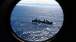 HMAS Success scans the southern Indian Ocean, near the coast of Western Australia, as a Royal New Zealand Air Force P3 Orion flies over, while searching for missing Malaysia Airlines Flight MH370. (AP Photo/Rob Griffith, File)