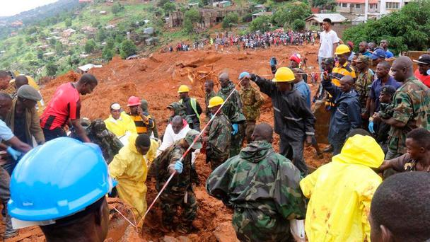 Rescue workers search for survivors after a mudslide in the Mountain town of Regent, Sierra Leone