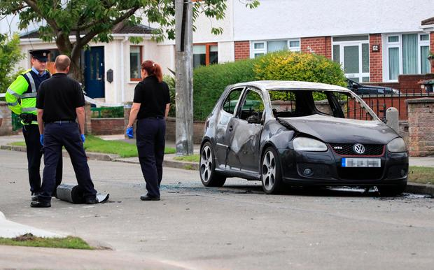 Gardaí examine the burnt-out getaway car on Santry Close in Dublin. Photo: Collins