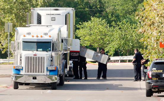 Police officers work on a crime scene after a number of illegal immigrants being smuggled into the United States were found dead inside a sweltering 18-wheeler trailer parked behind a Walmart store in San Antonio, Texas, U.S. July 23, 2017. REUTERS/Ray Whitehouse