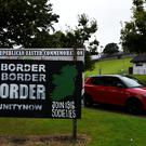 A car drives past a sign saying 'No Border, Hard border, soft border, no border' in Londonderry, Northern Ireland August 16, 2017. REUTERS/Clodagh Kilcoyne
