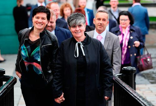 Civil partners Shannon Sickles, left, and Gráinne Close arriving at the High Court in Belfast yesterday. Photo: PA