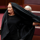 Australian One Nation party leader, Senator Pauline Hanson pulls off a burqa in the Senate chamber at Parliament House in Canberra, Australia. Photo: Reuters