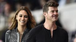 US singer Robin Thicke (R) and his girlfriend April Love Geary (L) attend the French L1 football match Paris Saint-Germain (PSG) vs Reims on May 23, 2015 at the Parc des Princes stadium in Paris. AFP PHOTO / FRANCK FIFE (Photo credit: FRANCK FIFE/AFP/Getty Images)